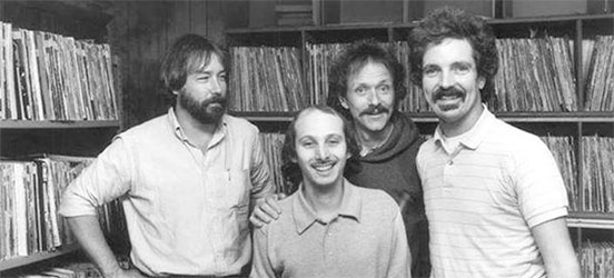 WHFS deejays, circa 1983. (WHFS deejays Damian Einstein (far right) and Weasel (front) pose with musician Jesse Colin Young (second from right) and an unidentfied record executive (far left) at WHFS headquarters in Annapolis, MD in 1983.  (Photo source: Handout photo/Steve King).