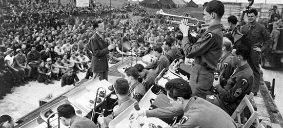 Major Glenn Miller directs his Army Air Force Band in a performance for U.S. and Allied troops in England, Jun-Dec 1944. Known as The Glenn Miller Band, this group played all over England and later France during World War II helping to boost morale of the troops serving in the European Theatre. (Photo Source: U.S. Air Force, Public Domain)