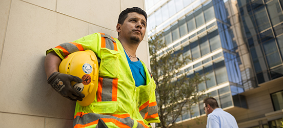 A male construction worker in a yellow vest leans against the wall of a building, helmet in hand.