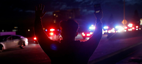 A man stands with his hands raised facing away from the camera, profiled against flashing police lights.