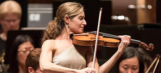 A standing woman plays the violin with a sublime expression on her face, in front of an orchestra in a concert hall.