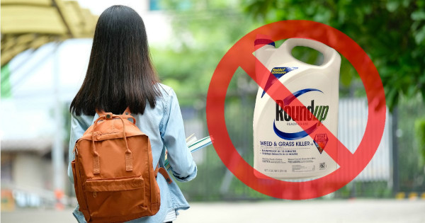 college university student with a backpack next to a bottle of Monsantos glyphosate herbicide ROUNDUP with a red circle and slash through it