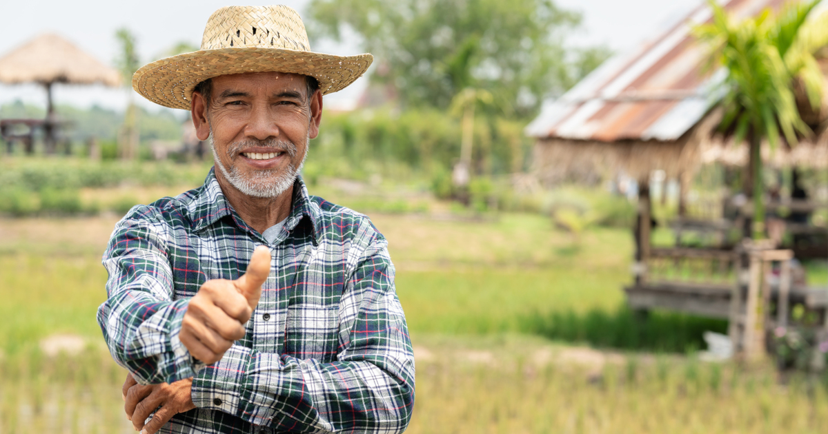 farmer in a crop field giving the thumbs up
