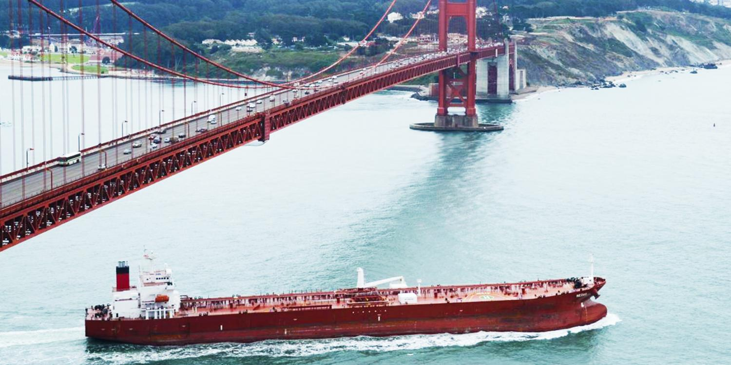 An oil tanker passes under the SF bridge