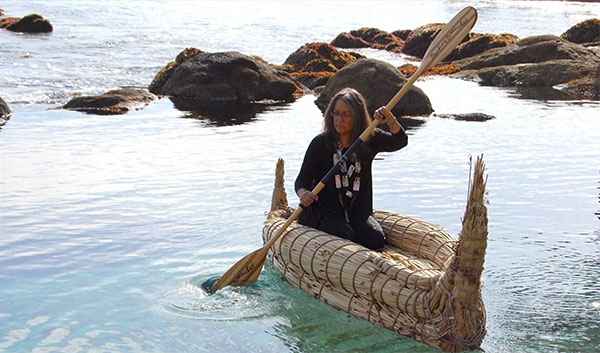 photo of a woman paddling a watercraft woven of reeds