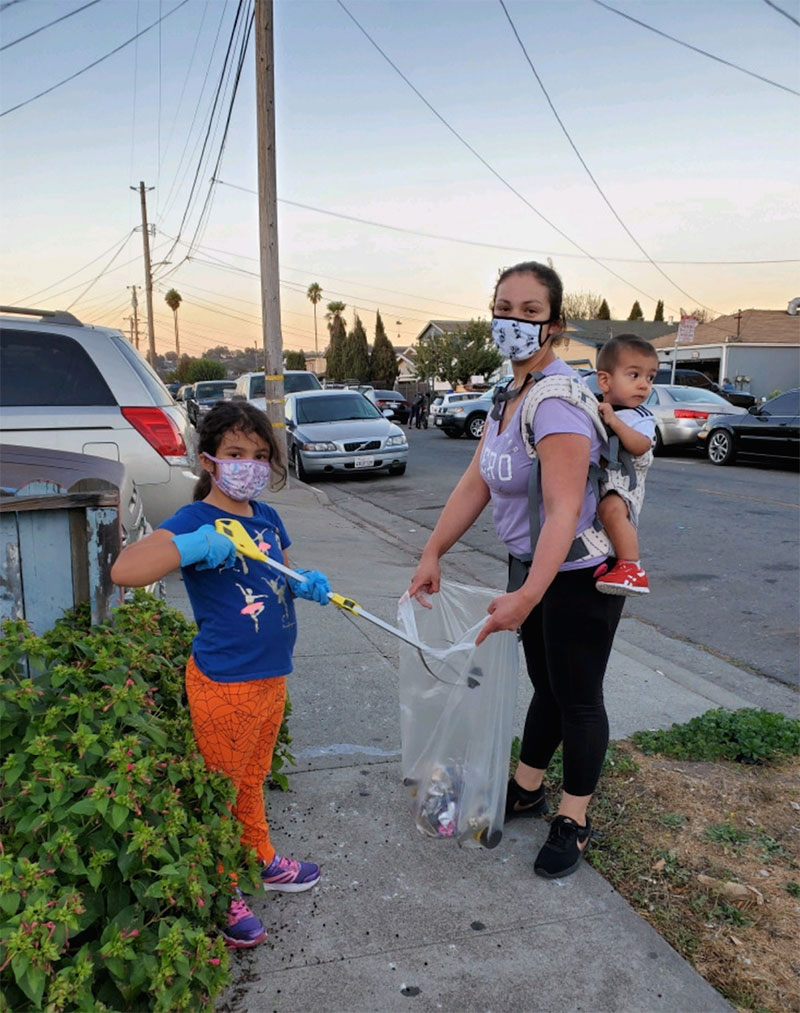 photo of a PPE-masked family collecting litter