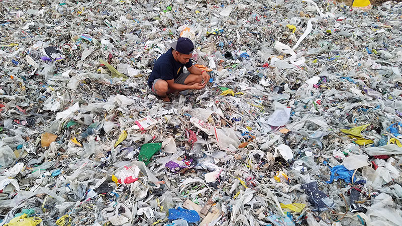 photo of someone sorting through a mountain of plastic discards